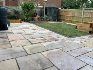 Indian Sandstone Patio with Artificial Grass and Sleepers in Kings Hill