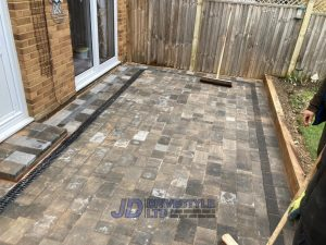 Patio with Retaining Sleeper Wall in Ashford